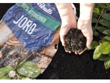 100 % återvunnen jord i händer vid rabatten