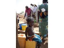 En pojke väntar på sin mamma som hämtar vatten.