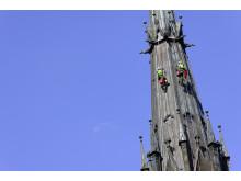 Två klättrare inspekterar tornen på Uppsala Domkyrka