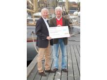 Göran Lindstedt tar emot checken på 41 341 kronor från Thomas Sandberg