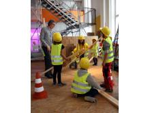 Kinder errichten zusammen einen Dachstuhl aus Holz
