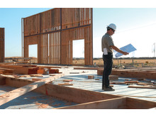 Man standing at construction site reading blue prints