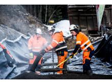 Mer enn 12 000 kubikkmeter Leca Lettklinker er blåst på plass på den 1,8 kilometer lange gang- og sykkelveien langs fylkesvei 152 i Trolldalen. Her er det Christoffer Løwen som styrer slangen og Ole Berg som raker på plass.