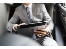 Businessman using HP tablet in back of private car