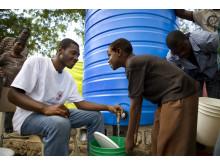 Frivillig i Haitis Röda Kors fyller hink med rent vatten