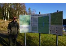 Friluftsutvecklare Robert Wahlström vid informationsskylt intill Bjursjön