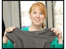 Annie Lööf visar upp klänningen som gjorts om till Ryggsäck