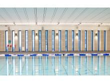 Åkeshovs sim- och idrottshall. Trä och smäckra fönsterpartier ramar in tillbyggnaderna