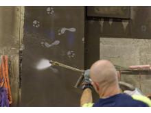 Gjutaren för högtryckssprutan över betongväggen