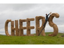 "Dom Joly building a giant ""cheers"" sign from straw bales as part of Nectar's ""cheers for ten years"" tour"