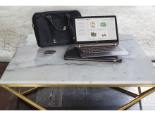 HP Spectre notebook with HP Spectre 14.0 Slim Topload, HP Spectre 13.3 Split Leather Sleeve and HP Bluetooth Mouse Z5000 on coffee table