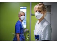 Personal i skyddskläder på infektionskliniken, utanför slussen till ett patientrum.