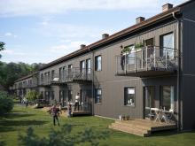 Illustration av trädgårdssida med altaner, balkonger samt gräsytor, BoKlok Krysset i Bålsta.