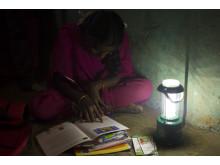 Aarathi läser läxan i ljuset av sin solcellslampa