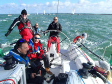 Story image - Ocean Signal - Sailor Simon Grier-Jones, pictured at the helm on another occasion, fell overboard while sailing in the Solent and was successfully recovered following the activation of his Ocean Signal rescueME MOB1