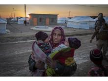 Kvinna med barn som flytt striderna i Mosul, Irak.