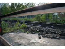 Konventionell järnväg möter järnvägsräls på solig betongplatta