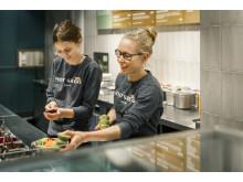 Medarbetare serverar sallad.