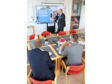 Erhvervsministeren bliver her orienteret af Forenede Service's adm. direktør Hans Fog