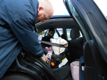 PRECIOUS CARGO: Casualty reduction officer Stuart Howarth showing a parent the correct way to thread the seatbelt