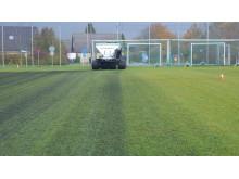 Biokol sprids ut på gräsplanen, vilket sedan myllas ner i jorden.