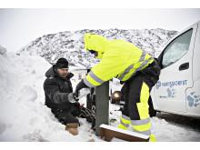 Reparerer kabelskap i snøen