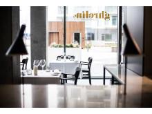 Bordpladen har integrerede Arne Jacobsen lamper, der her fungerer som varmelamper.