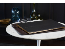A HP Spectre x360 Special Edition sitting on a table on top of a HP 13.3 Leather Sleeve HP20150901993