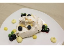Pavlova served with white chocolate cream, lime curd and blueberries