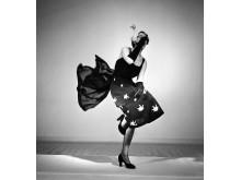 Straw and chiffon är fotografens titel på studiofotot från 1950 där en livligt poserande modell visar klänning från varuhuset MEA. Foto: Sten Didrik Bellander, © Nordiska museet