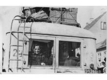 Kvinde i bagruden på en hvid bus