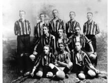Ett fotbollslag bestående av allvarliga unga män i randiga tröjor. Ateljébild från sekelskiftet 1900-talet. Foto: Hedvig Rosendahl, Nordiska museet.