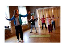 Volontär som håller i dans och sångträning för barn.