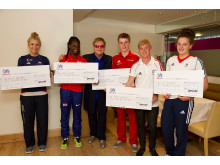 Five SportsAid athletes receiving cheques from Elton John on 28 June 2014