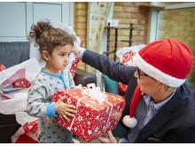 Flicka på asylboende får julklapp av en av Mimers anställda