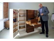 """Designer Günther Rothe stellt seinen """"Schuhschrank mit Extras"""" vor. Neben Platz für 16 Paar Schuhe, bietet der Schrank unter anderem Raum für Pflegemittel und Schuhanzieher."""