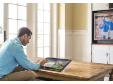 Man using the HP ENVY ROVE 20 Mobile All-in-One in reclined mode while watching TV in living room
