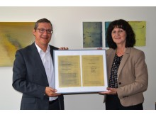 Kommunalbetreuer Frank Schneider übergab eine gerahmte Kopie des ursprünglichen Vertrags an Bürgermeisterin Helga Schmidt-Neder.