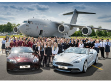 School pupils, teachers and RAF personnel are pictured alongside Aston Martin vehicles at RAF Brize Norton in Oxfordshire.