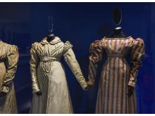 Kappa och klänning från ca 1825 i utställningen Uppklädd