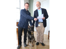 Nationalmuseets direktør Per Kristian Madsen overrækker  danefædusør til hunden Django, som fandt kostbare guldringe