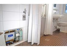 Halbhohe Duschtür in ebenerdiger Dusche mit SANFTLÄUFER-Installation