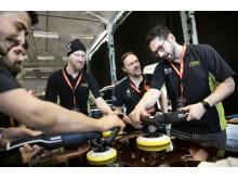 Alex Ghanati från Future Car Care finslipar tekniken vid övningsstationen för roterande polering. Jason Rose coachar.