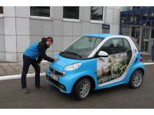 """Foto: Mit dem """"50 Jahre Jugend forscht E-Smart"""" trifft das Patenunternehmen Bayernwerk ehemalige bayerische Preisträger, hier Lukas Kerner, und lässt diese das Elektroauto signieren."""