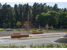 Generös lekyta med klättertorn och asfaltskullar som är upplyst kvällstid.