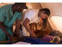 Två medarbetare från Läkare Utan Gränser undersöker en patient i flyktinglägret i Yida, Sudan. Foto: Camille Lepage.