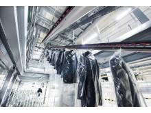 Med det hængende conveyorsystem kan beklædningsgenstande automatisk transporteres mellem niveauerne på lageret til hængende tekstiler.