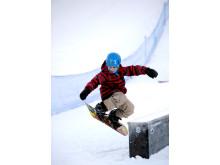 Liten kille åker snowboard på World Snow Day