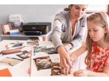 Kvinne og barn med fotoutskrifter og HP skriver