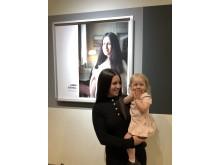 Anna Ekvall med dottern Annabelle framför sitt porträtt